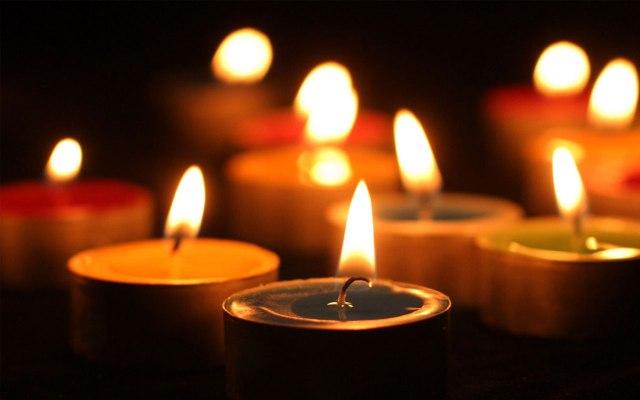 Lit tea light candles against a dark background