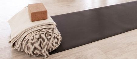 A dark grey yoga mat, with a cork block, grey-and-white bolster pillow, and folded white blanket stacked at one end